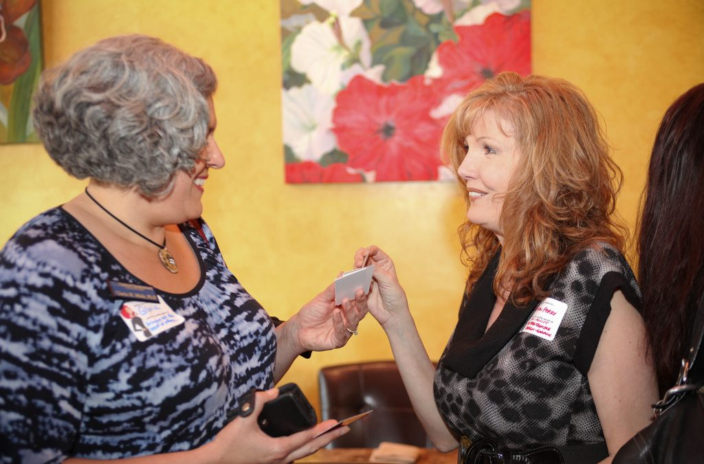 photo of 2 women exchanging business cards