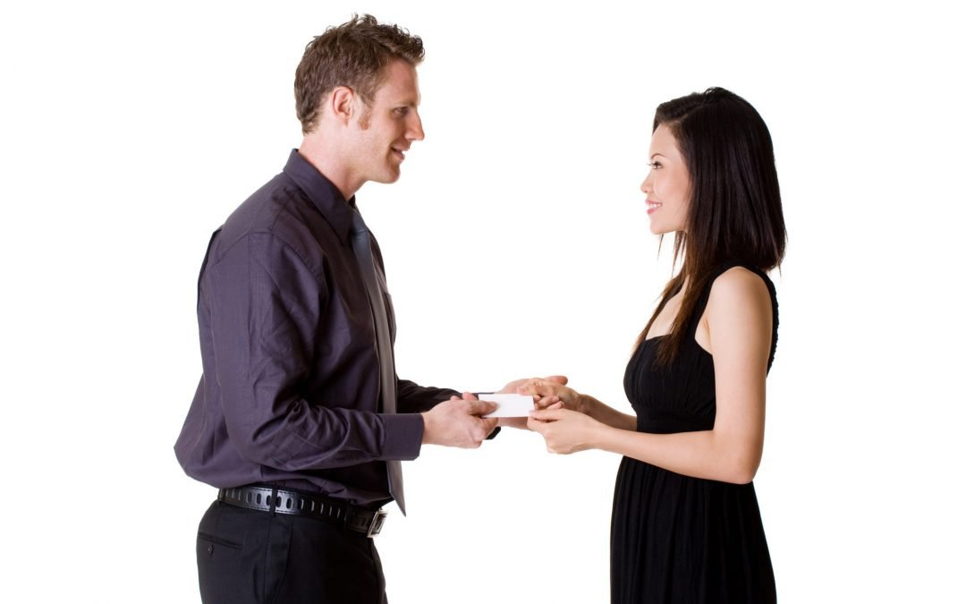 man and woman exchanging business cards, she is in a formal dress with no pockets